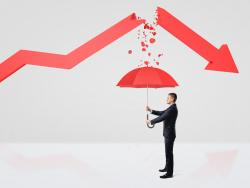 Businessman protecting himself from broken trend line with red umbrella