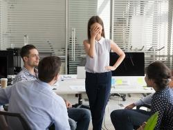 Embarrassed employee hiding her face with her hands at business meeting