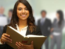 Female student holding a book with professionals in the background