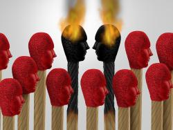 Two lit matchsticks being used as a metaphor for two employees having a work conflict.