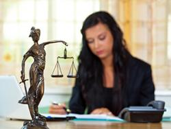Lady Justice and her scales with a paralegal seated in the background.