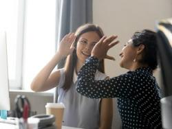 Photo of two women at a work station, giving each other a high five