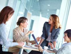 Women in professional attire talking together