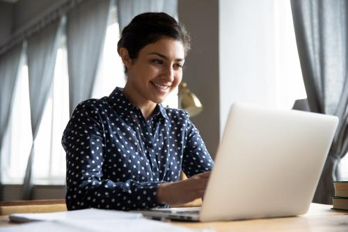A woman sitting at home in front of her laptop working on distant learning